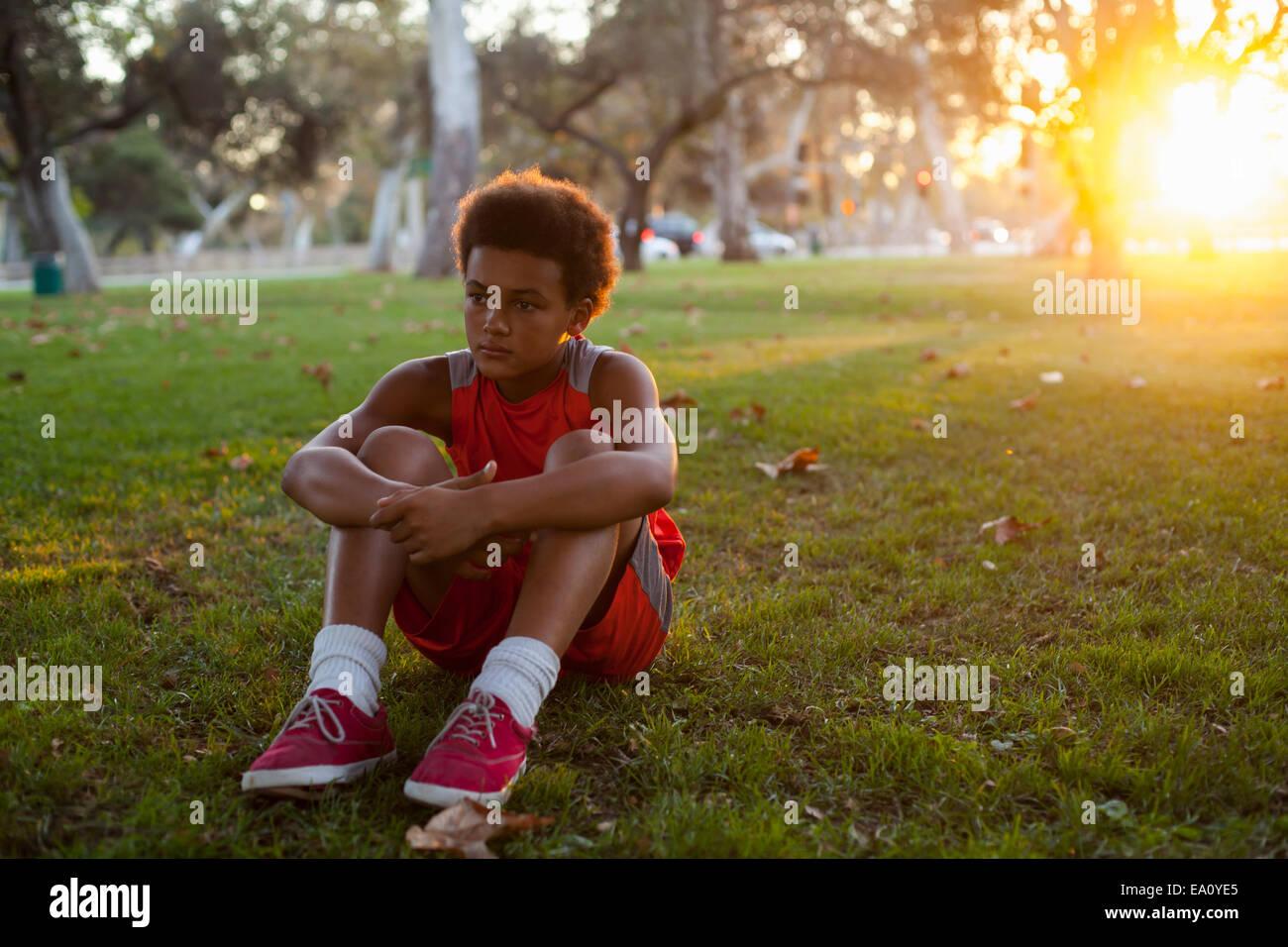 Traurig aussehende junge sitzt im park Stockbild