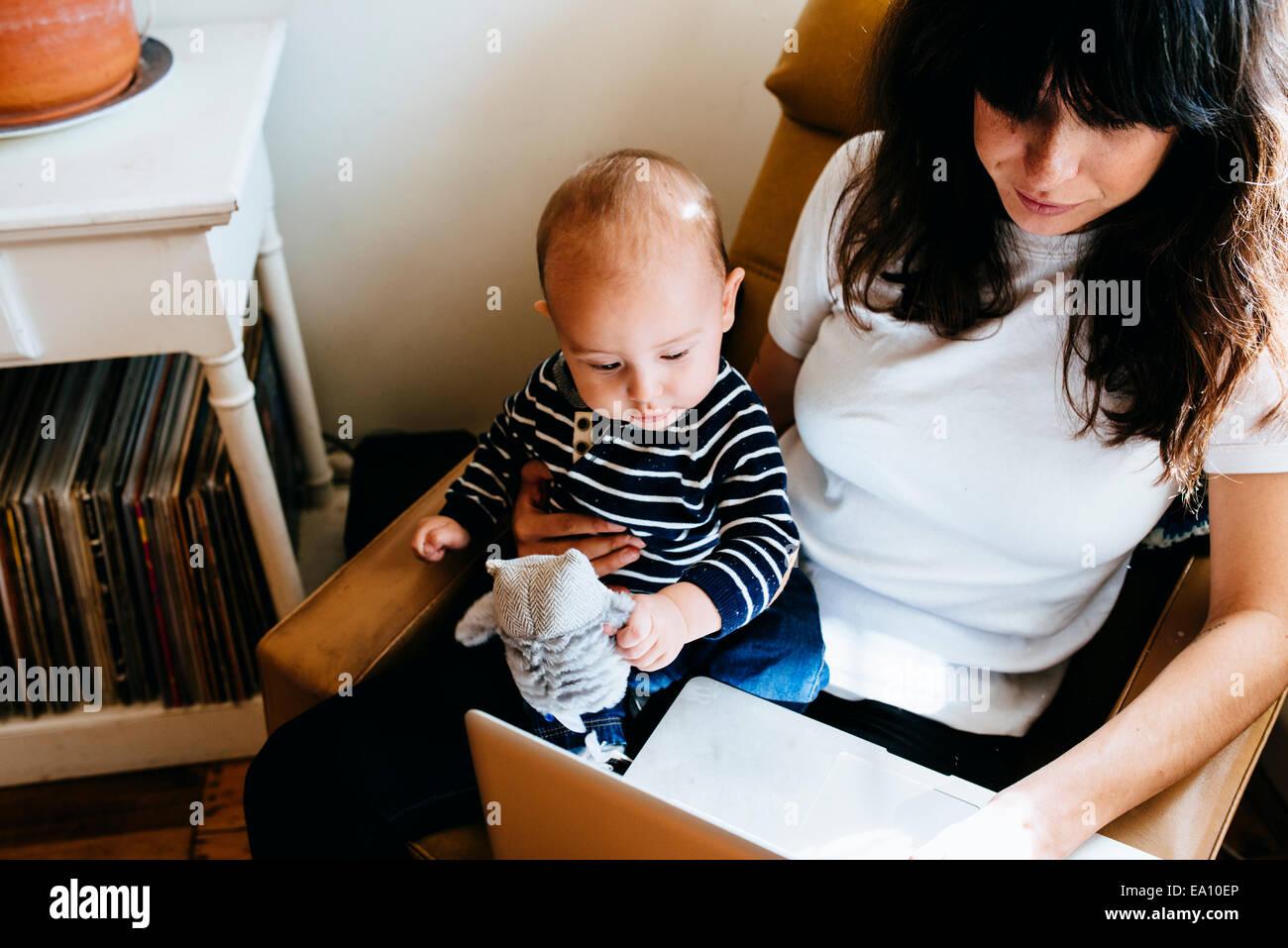 Mutter mit Laptop mit Sohn auf Schoß Stockbild