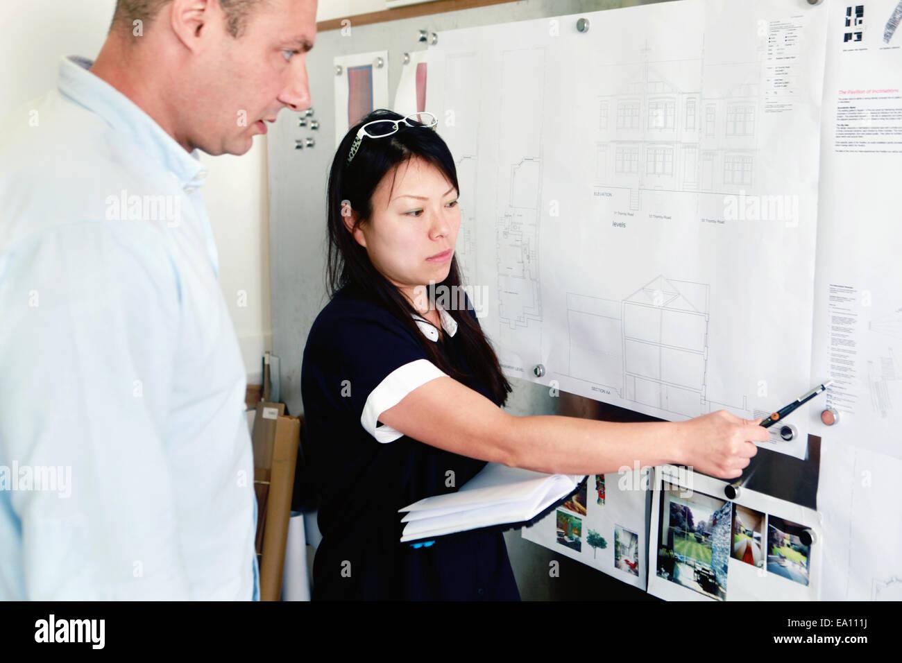 Männliche und weibliche Architekten besprechen Ideen im Büro Stockbild