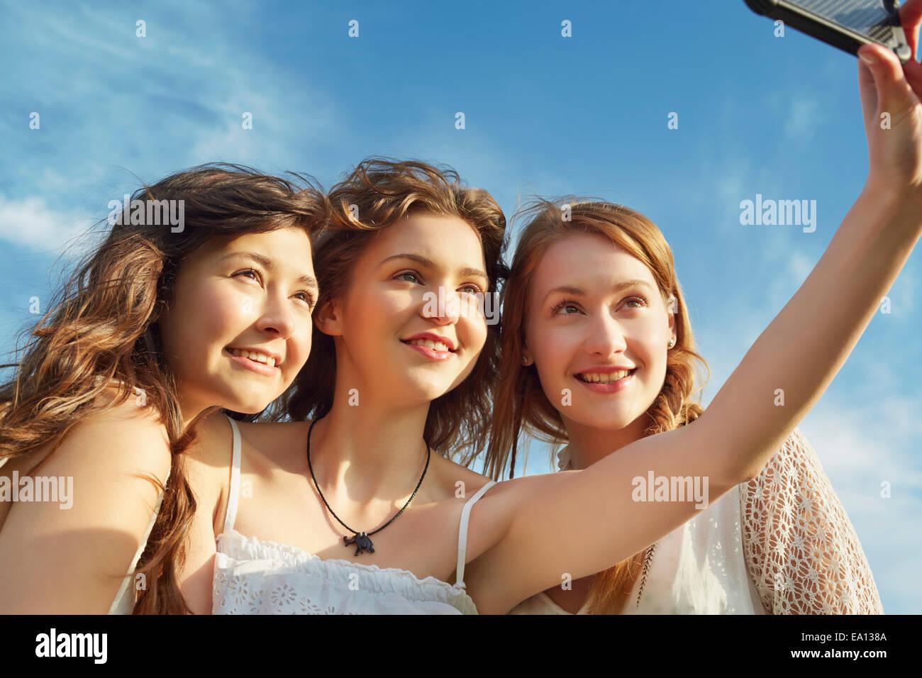 Drei junge Frauen Lächeln für Selfie auf smartphone Stockbild