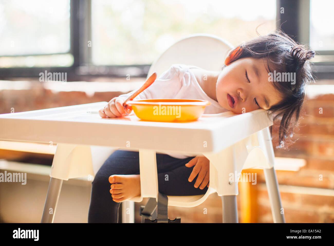 Einjähriges Mädchen schlafend im Hochstuhl beim Frühstück Stockbild