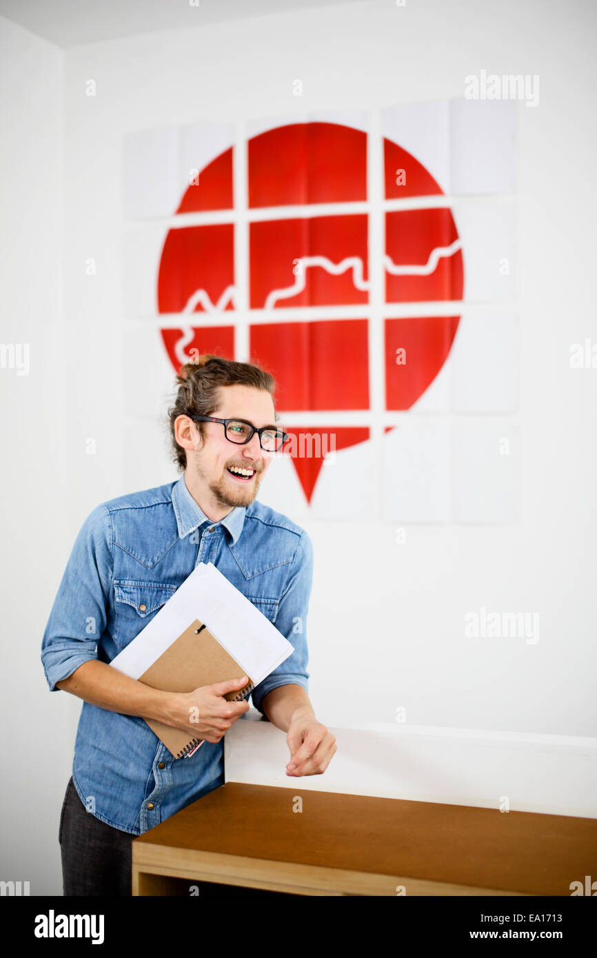 Junger Mann im Konstruktionsbüro, Lächeln Stockbild