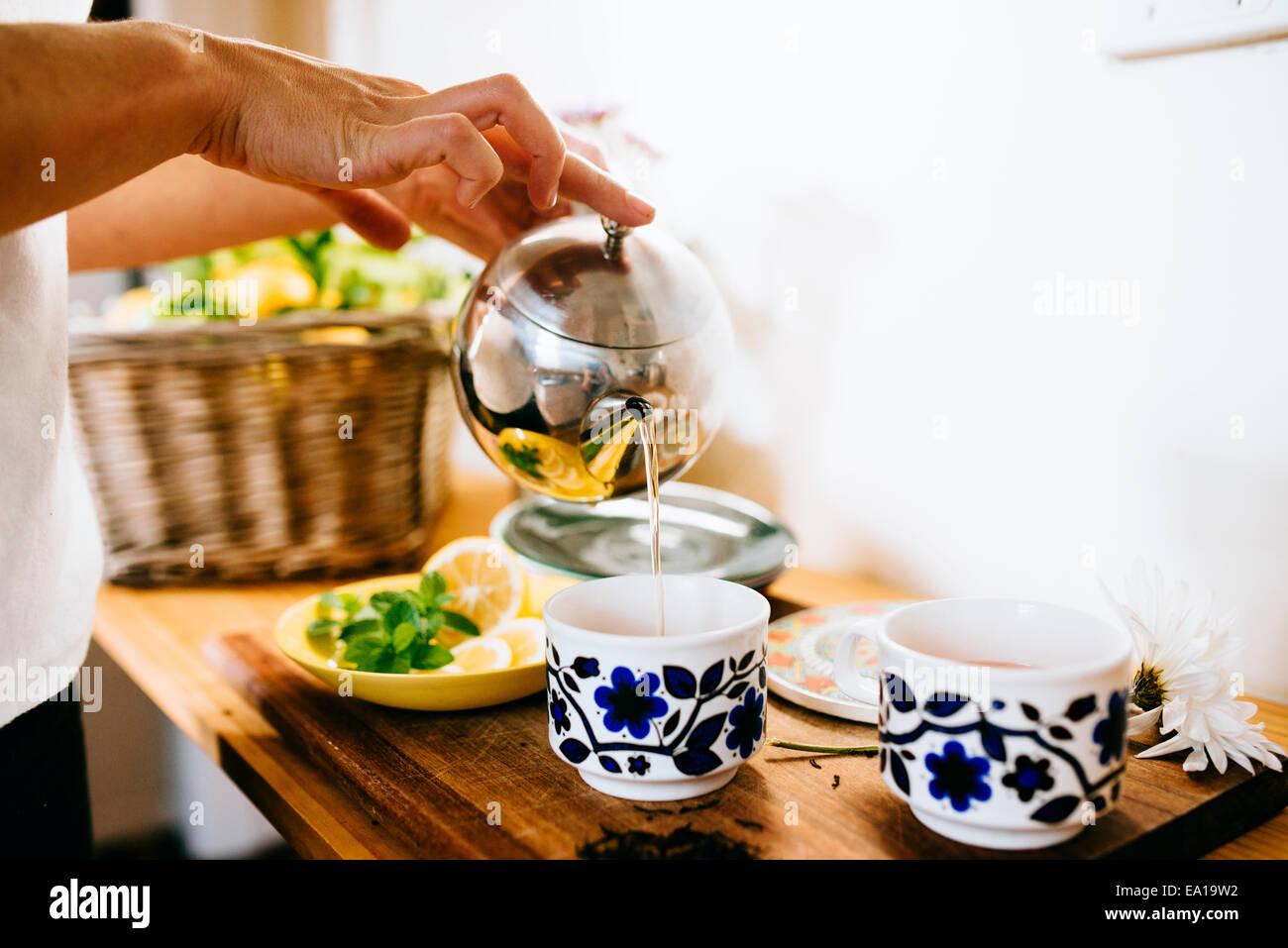 Frau, Zitrone und Minze Tee zubereiten Stockbild