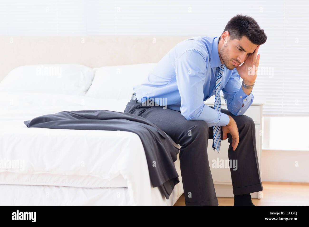 Stirnrunzelnd Geschäftsmann am Bettrand sitzen Stockbild