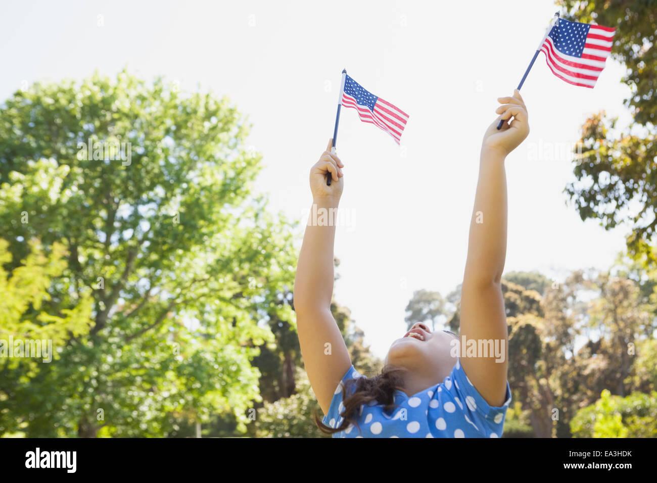 Mädchen hält zwei amerikanische Flaggen im park Stockbild