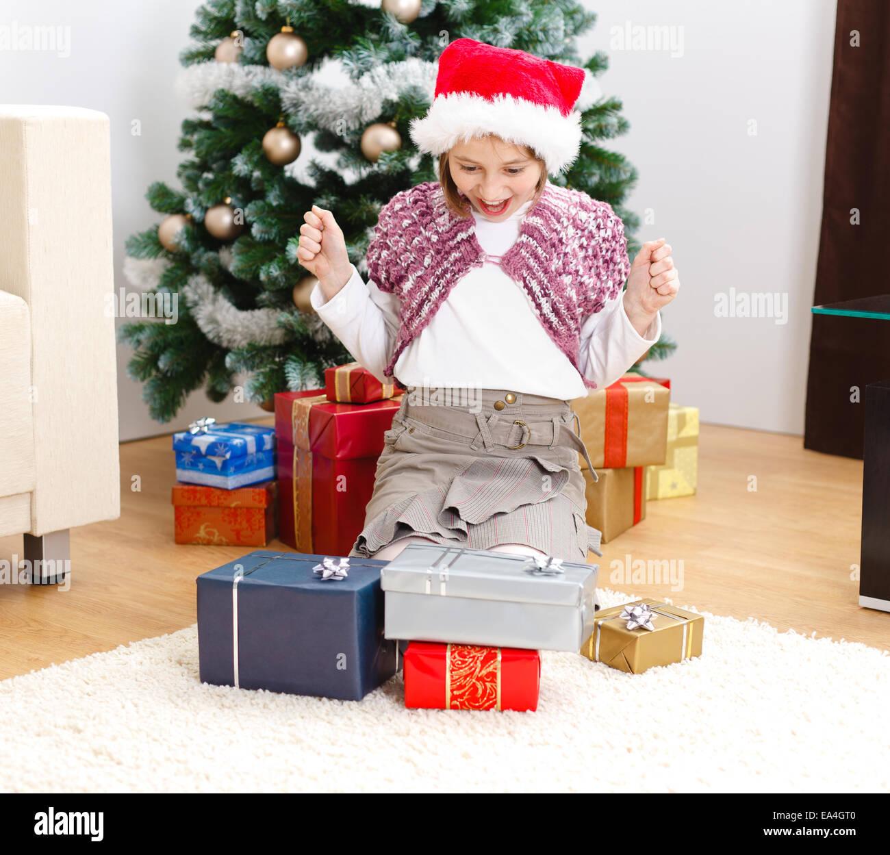 Glückliches Mädchen betrachten viele Geschenke vor Weihnachtsbaum ...