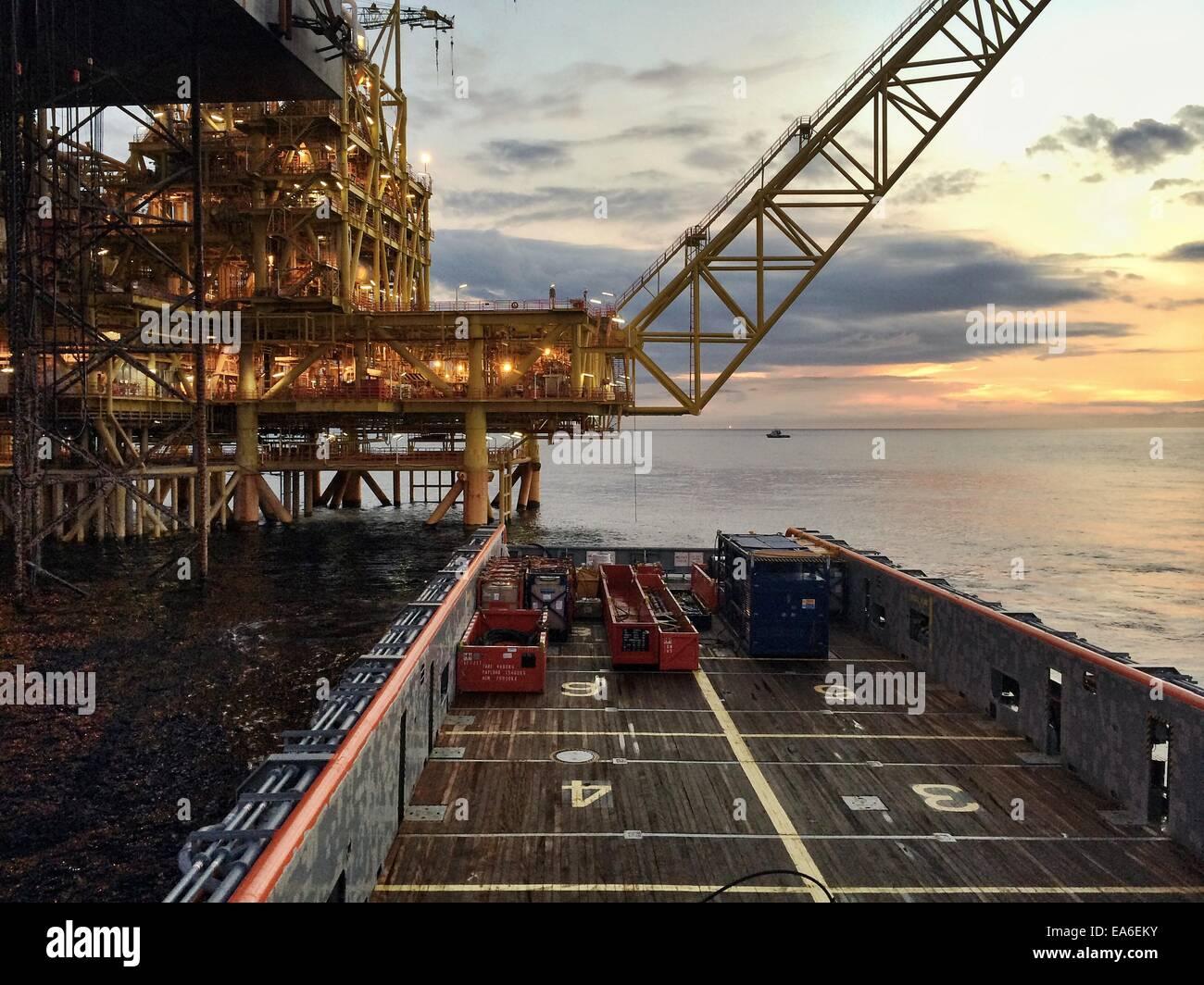 Zentrale Verarbeitung Ölplattform auf Cargo-Betrieb mit Offshore-Schiff bei Sonnenaufgang Stockbild
