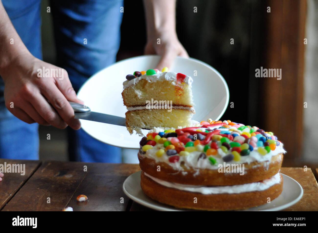 Man schneidet ein Stück Geburtstagstorte Stockbild