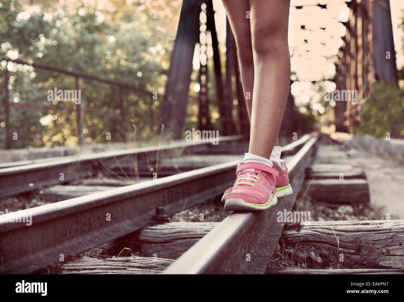 Nahaufnahme der Frauenbeine entlang Schienen Stockbild