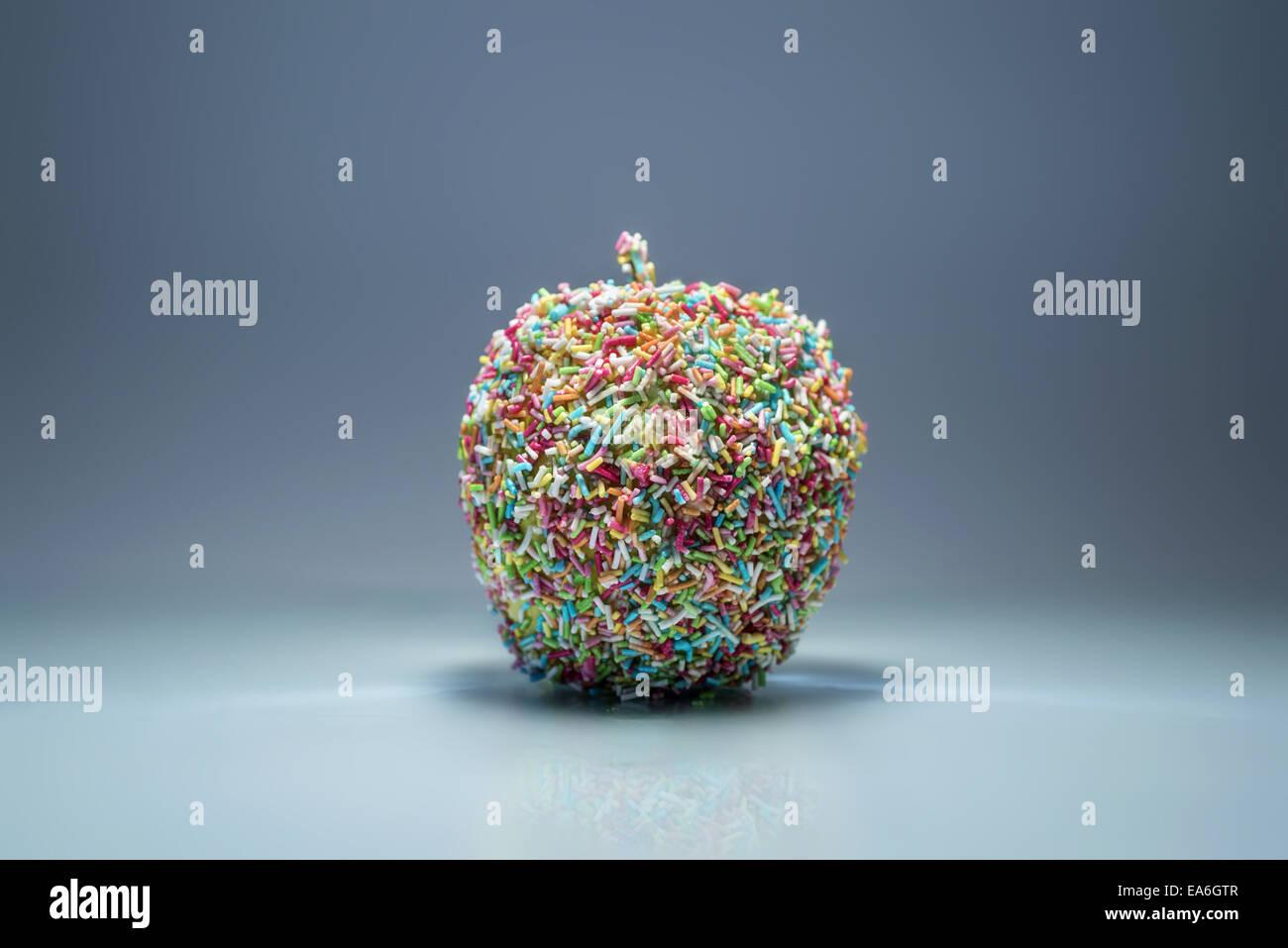 Apple mit bunten Streuseln bedeckt Stockbild