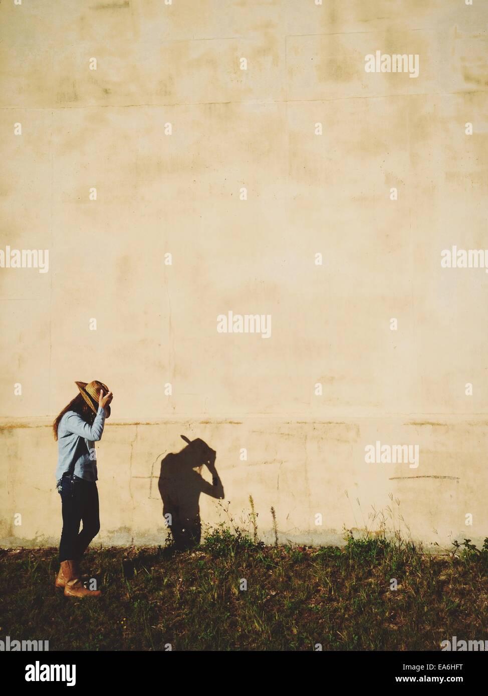Mädchen in Cowboy-Hut auf Schatten suchen Stockbild
