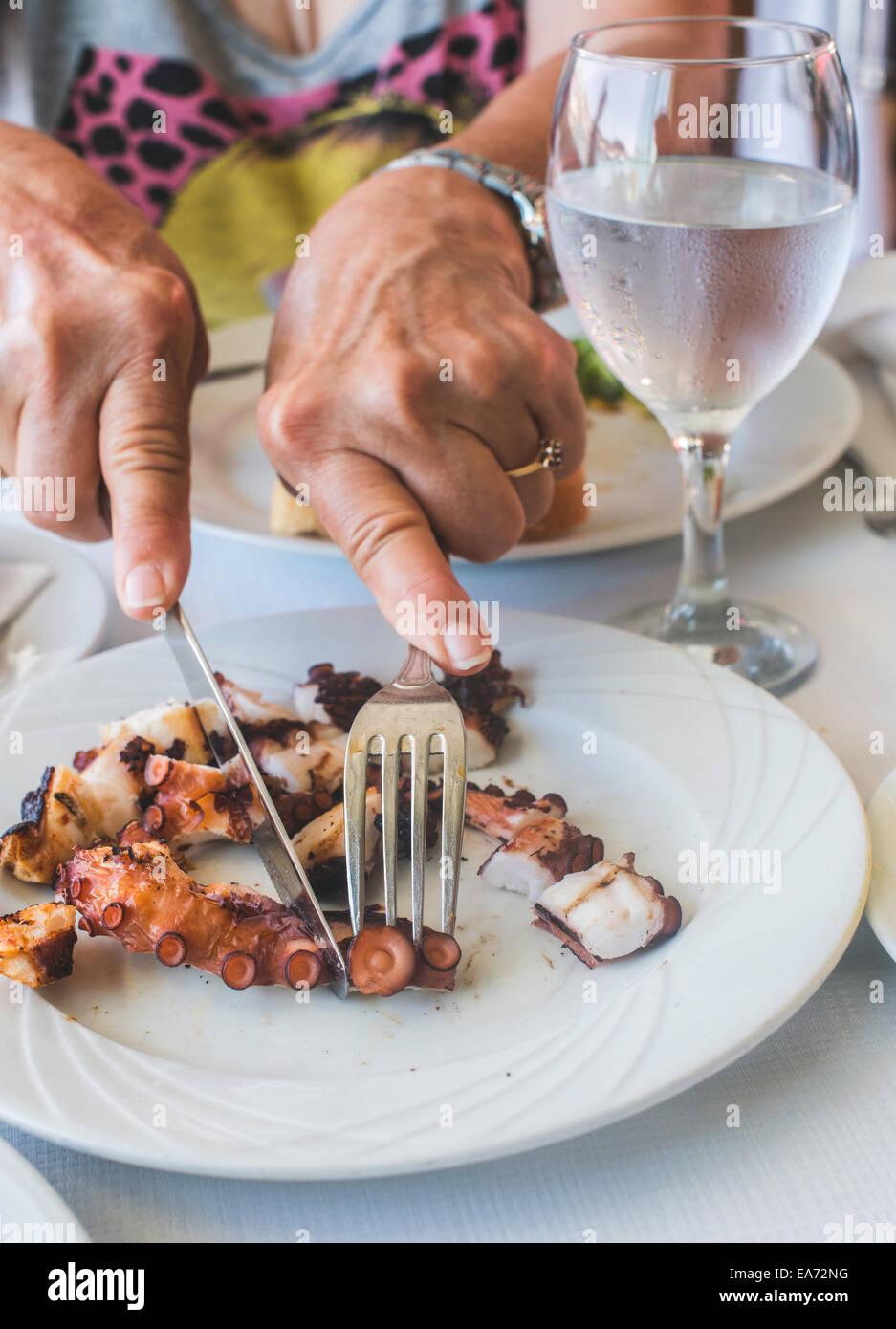Oktopus in einem griechischen Restaurant. Hände sind schneiden Krake Stockbild