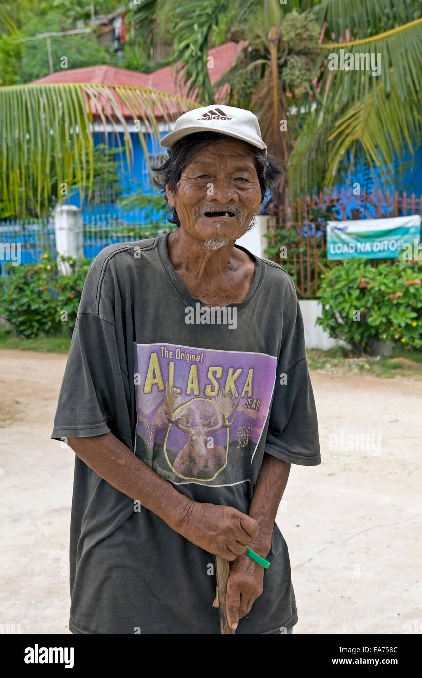 Ein Filipino Greis mit Arthritis stützt sich auf seinen Spazierstock in Guimaras Island, Philippinen. Stockbild