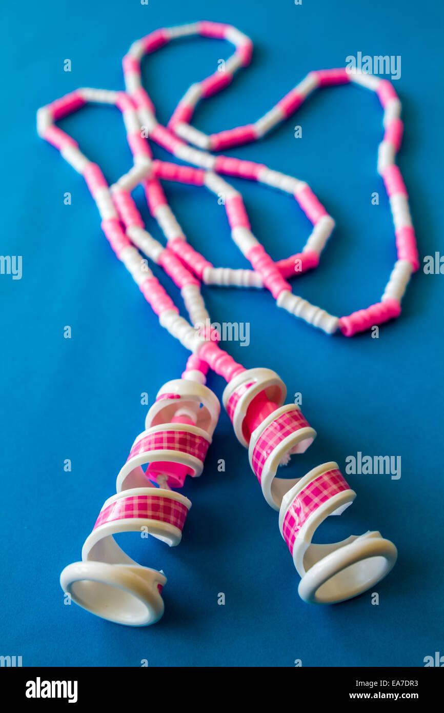 Rosa und weiße Spielzeug Springseil auf blauem Hintergrund Stockfoto