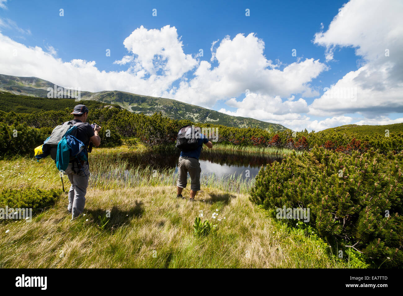Zwei kaukasische Wanderer mit Rucksack wandern rund um einen See in den Bergen Stockfoto