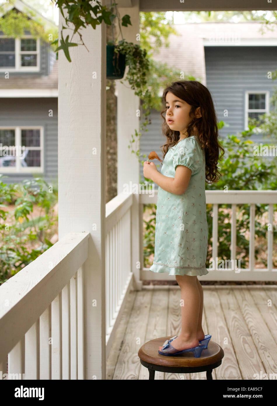 junges Mädchen im Spiel Schuhe stehen auf Hocker auf Veranda Stockbild