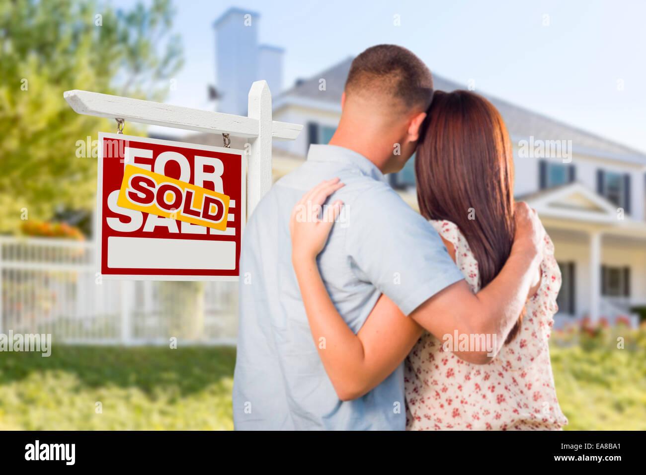 Für Immobilien Verkaufsschild und liebevolle militärische paar Blick auf schöne neue Haus verkauft. Stockbild