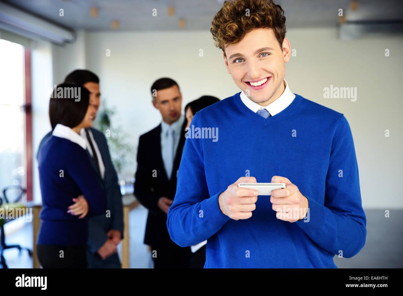 Glücklich Kaufmann mit Smartphone vor einem Kollegen Stockbild