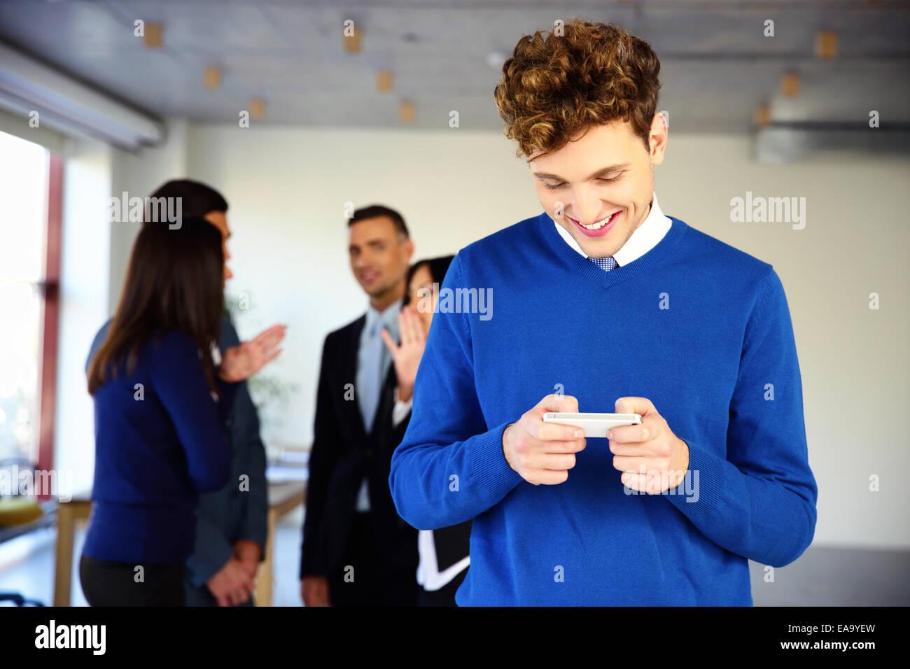 Lächelnde Geschäftsmann mit Smartphone vor einem Kollegen Stockbild