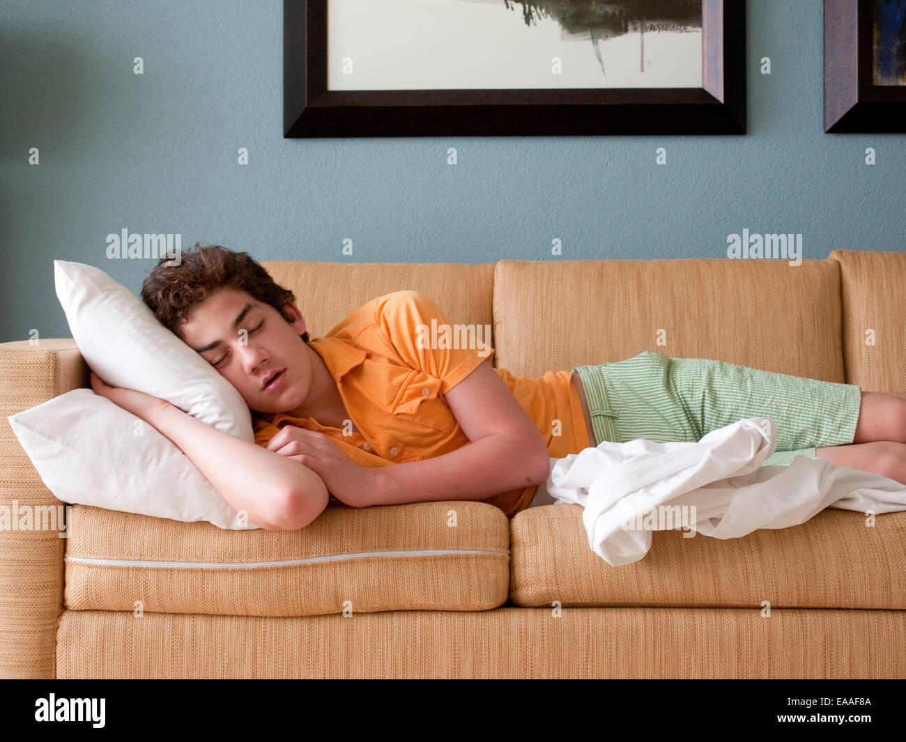 junger Teenager auf Schlafcouch Stockbild