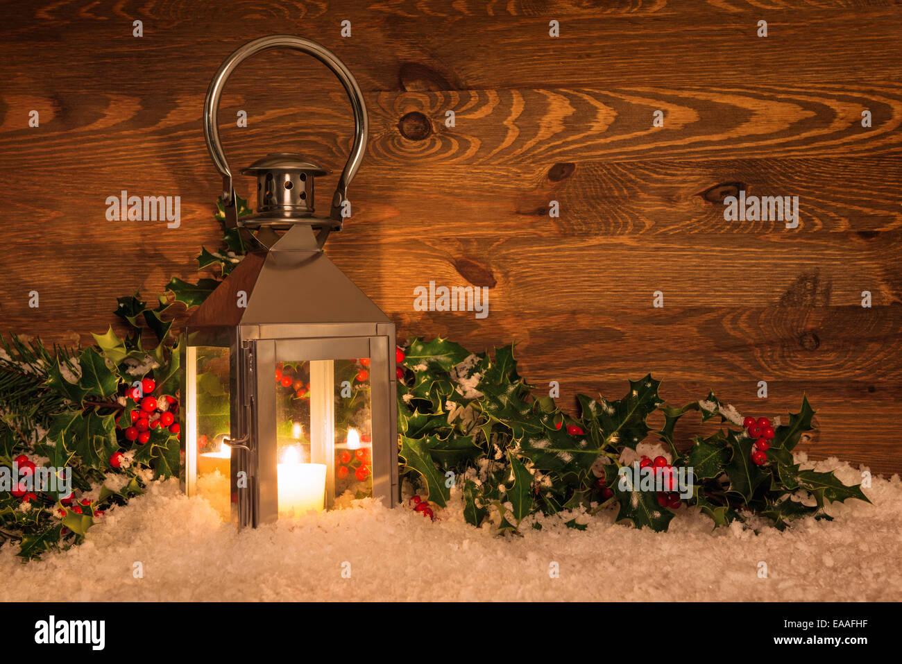 weihnachten kerze laterne im schnee von holly mit roten beeren gegen einen rustikalen holzm beln. Black Bedroom Furniture Sets. Home Design Ideas