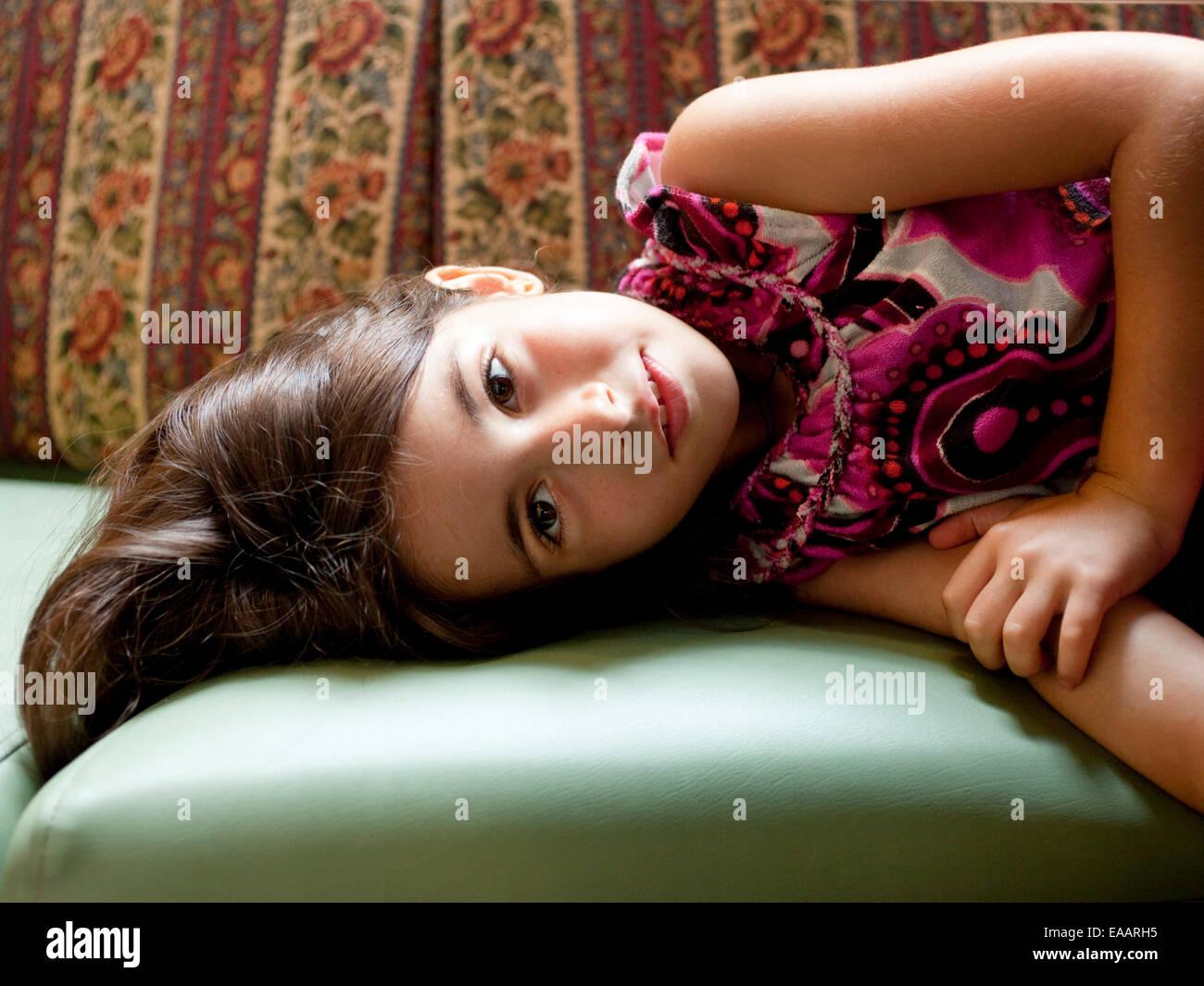 Mädchen auf der Couch liegend Stockbild