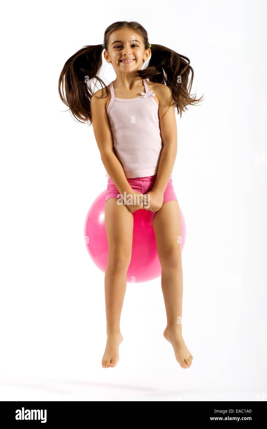 Mädchen auf einem springenden Ball spielen Stockbild