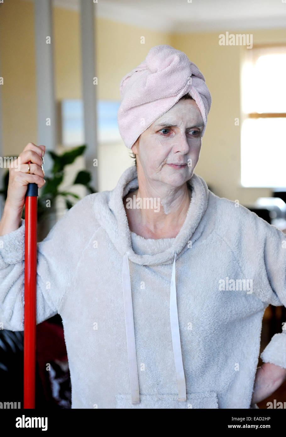 Applying Frau Weibchen tragen einen Turban auf das nasse Haar und mit einer Gesichtsmaske Gesundheit und Schönheit für die Haut Stockfoto