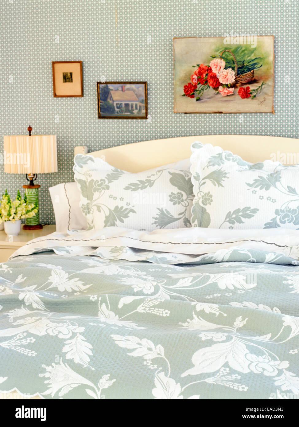 Bett mit floral gemusterte Decken und Kissen Stockbild