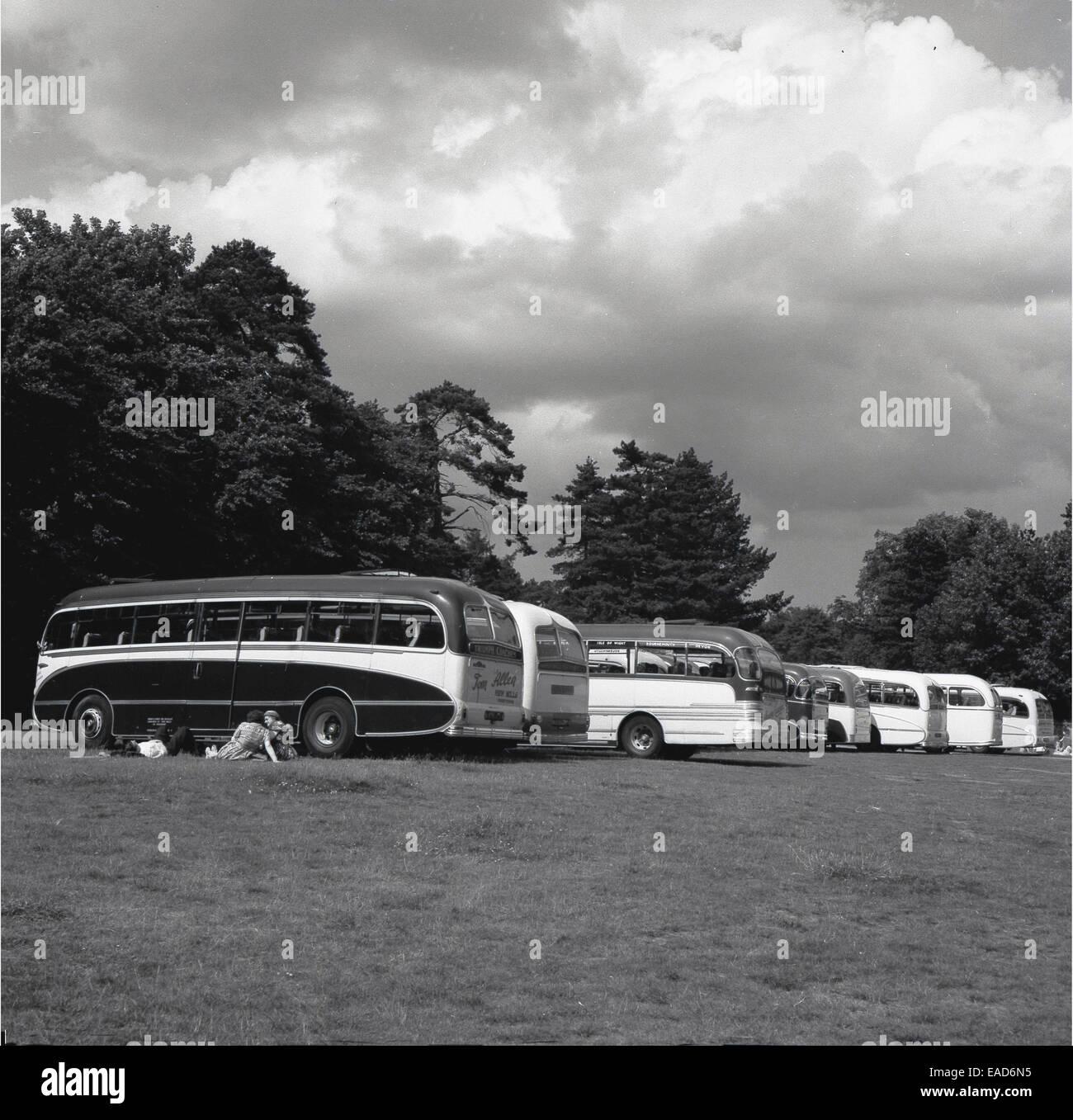 historische. Linie der Reisebusse in einem Feld der 1950er Jahre. Stockbild