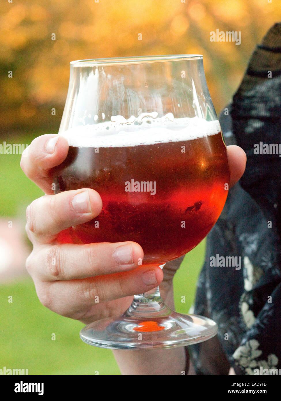 hält ein Glas Bier während Sie Tür-cocktail-Empfang Stockbild