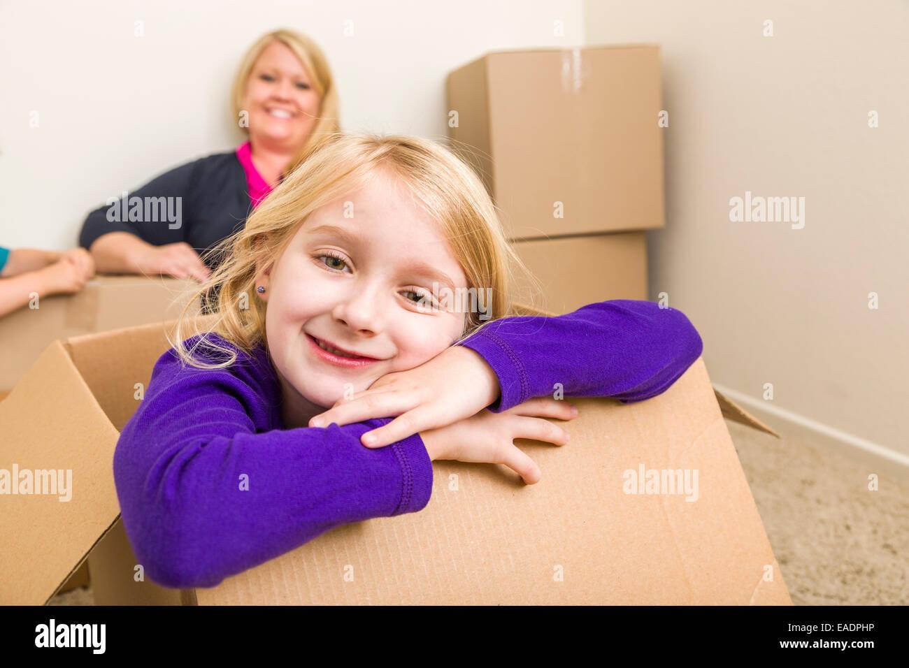 Glückliche junge Mutter und Tochter Spaß mit Umzugskartons. Stockbild