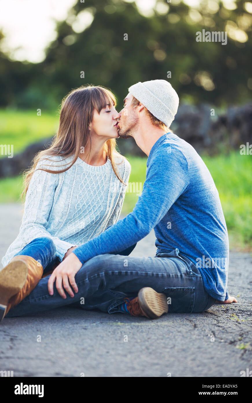 Glückliche junge Paare, die Spaß im Freien. Romantisches Paar küssen in der Liebe auf der Landstraße. Stockfoto