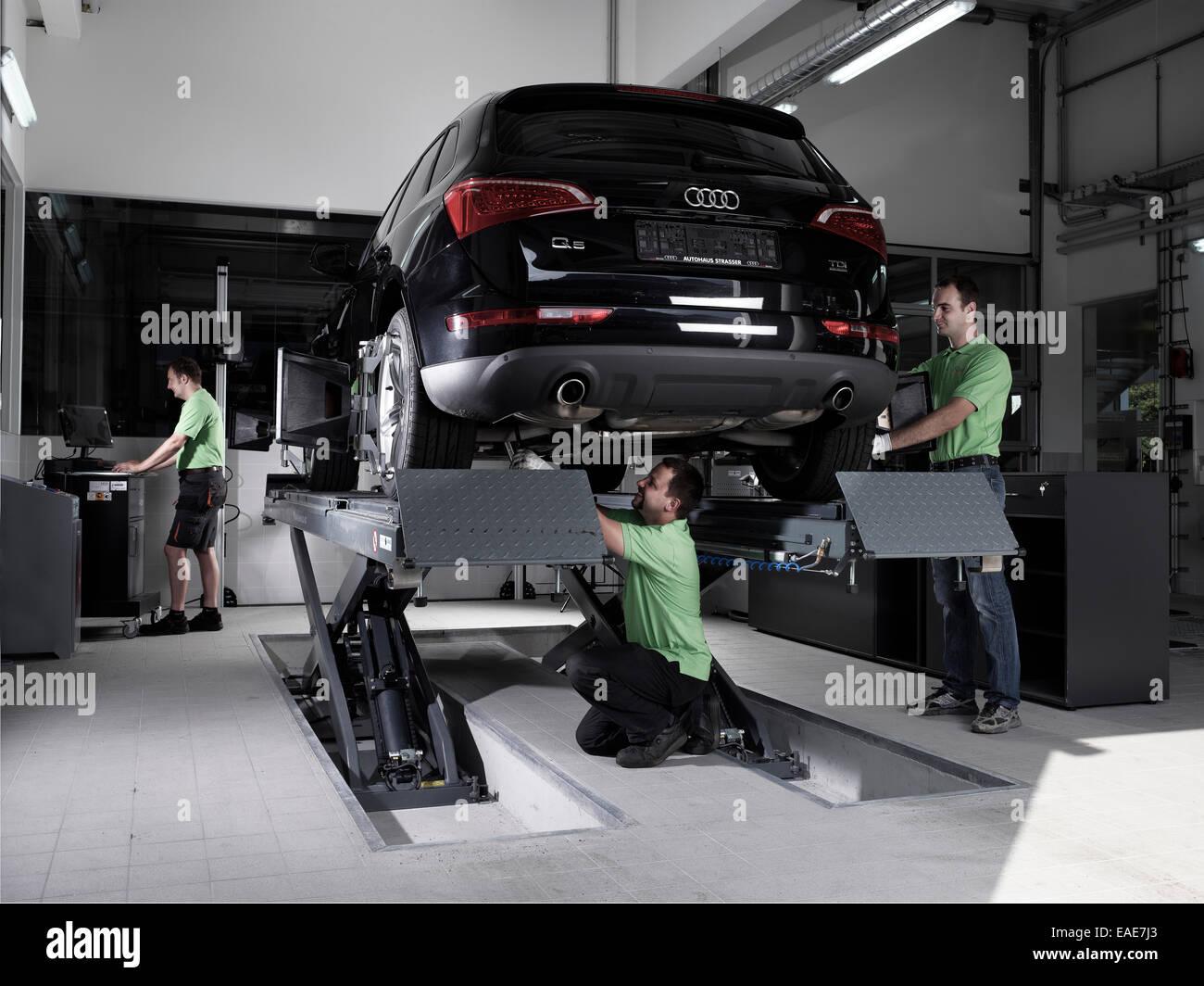 Mitarbeiter Montage Platten Rad Ausrichtungen, VW Strasser, Volkswagen Auto verfolgen reparieren Shop, St.Gertraudi, Stockbild