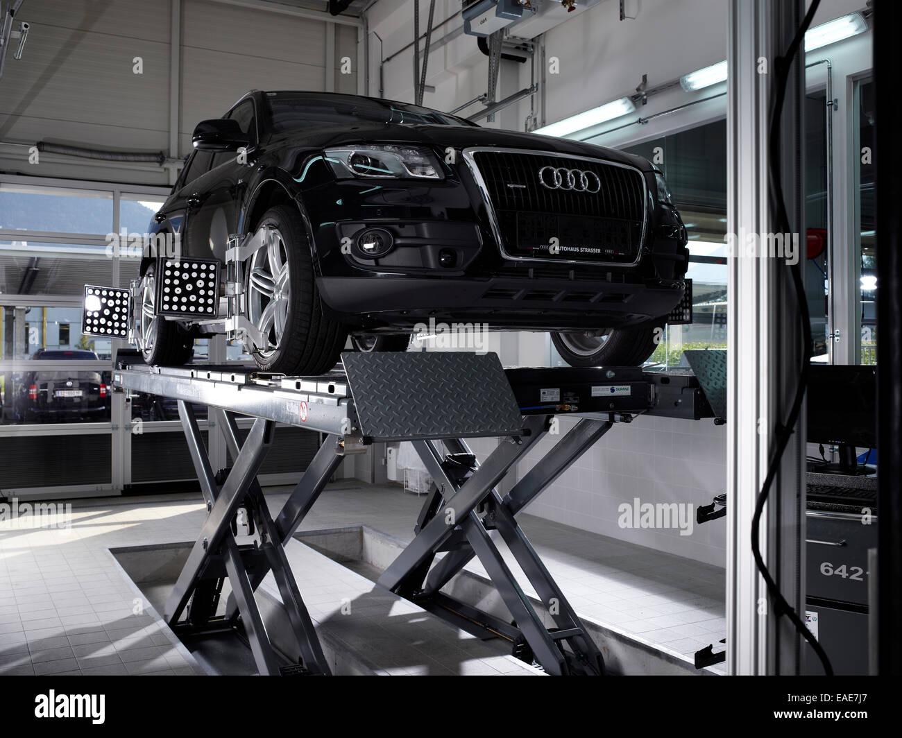 Auto auf einer Hebebühne steht mit angepassten Druck Prüfbleche für die Achsvermessung, Auto-Werkstatt, Stockbild