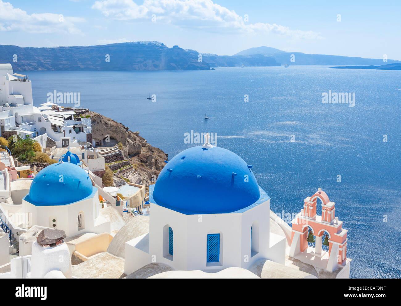 Weiße griechische Kirche mit blauer Kuppel & rosa Glockenturm, Oia, Santorini, Thira, Kykladen, griechische Stockbild