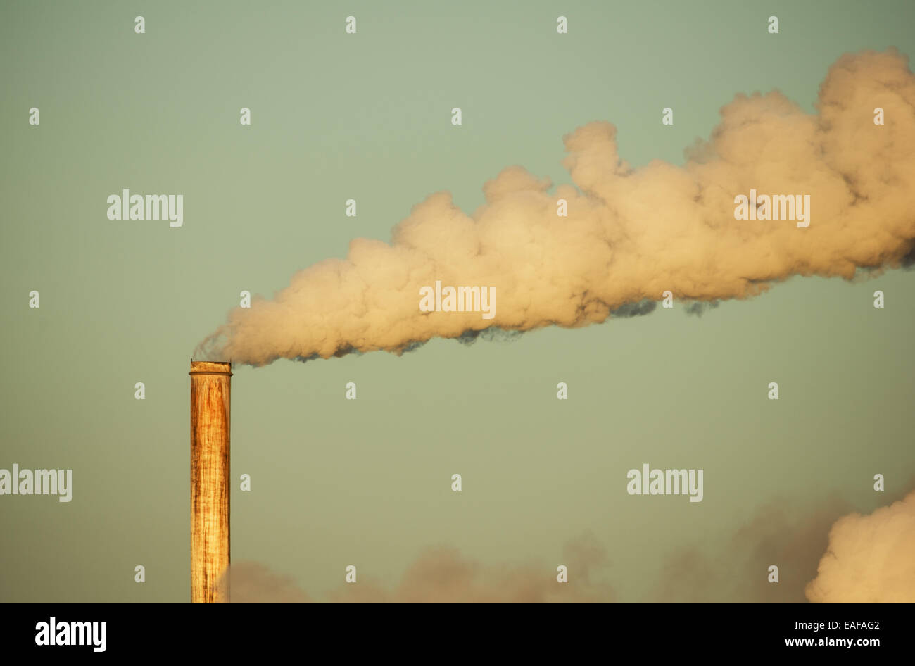 alte rostige Schornstein mit Rauchfahne von frühen Morgenlicht beleuchtet Stockbild