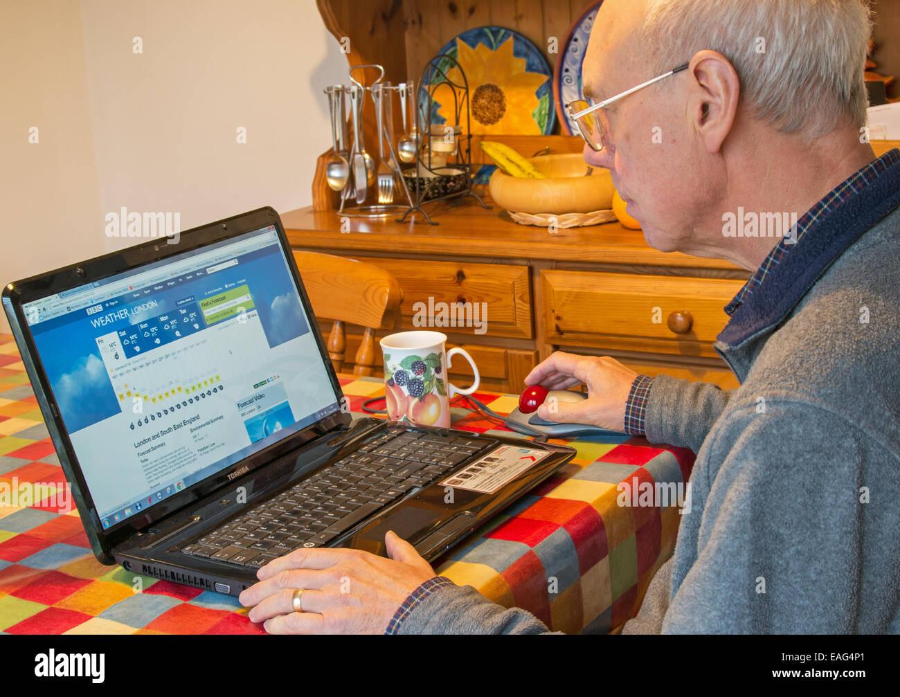 Pensionierter Mann schaut auf BBC UK Wettervorhersage mit einem Laptopcomputer. Stockbild