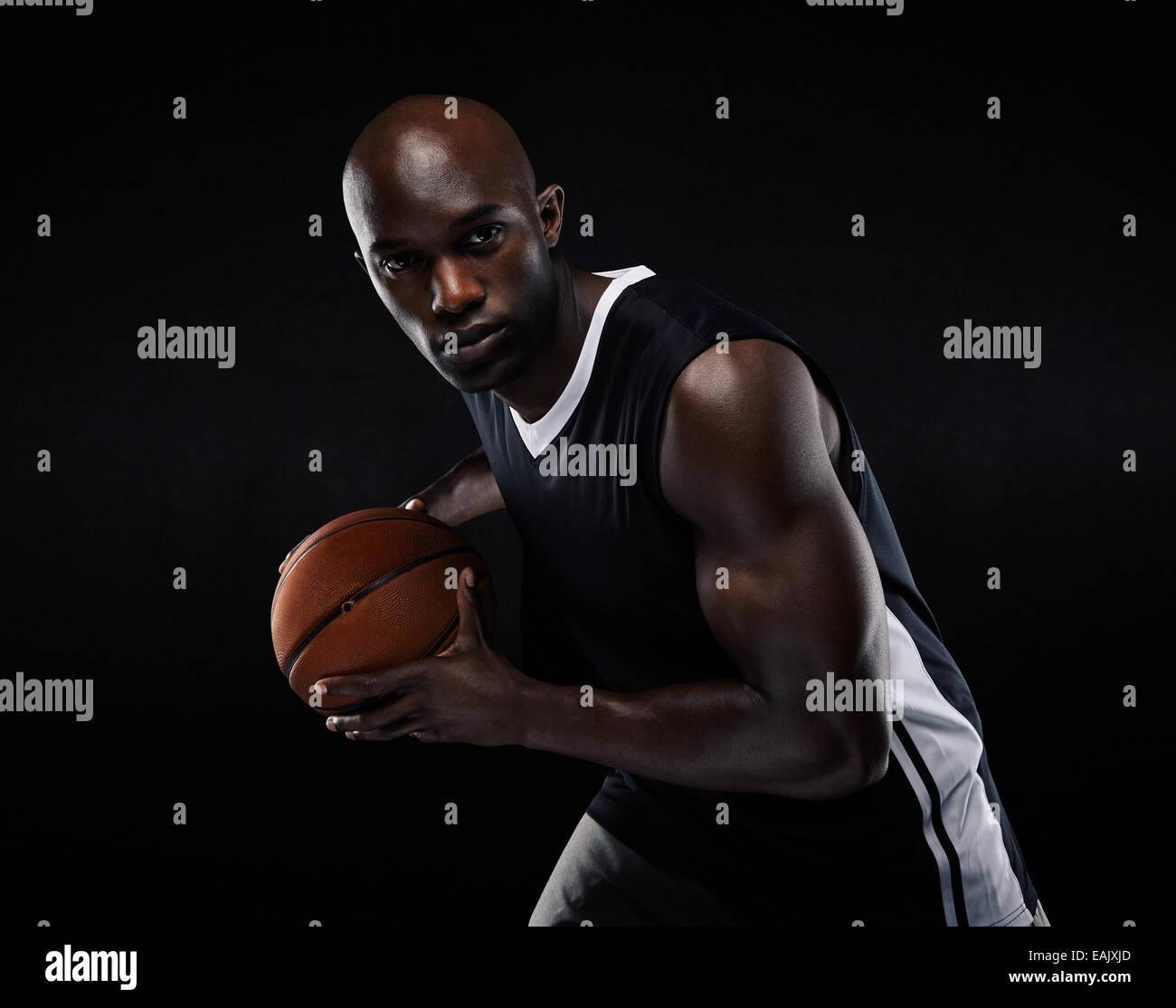 Porträt von Fit jungen männlichen Athleten Basketball zu spielen. US-amerikanischer Basketballspieler auf schwarzem Stockfoto