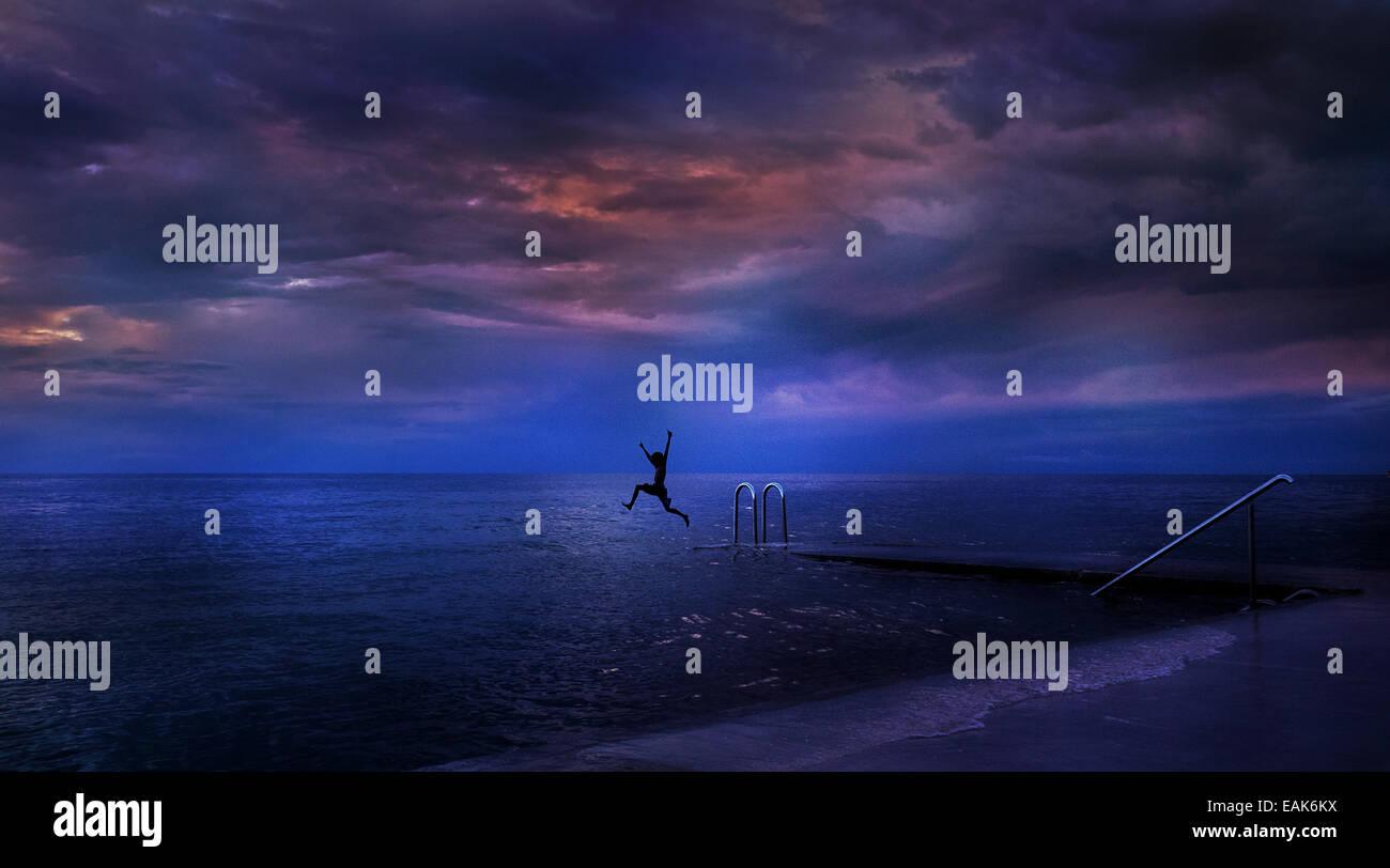Ein Farbfoto Landschaft einer Person in der Silhouette springen ins Meer in Slowenien, Europa Stockbild
