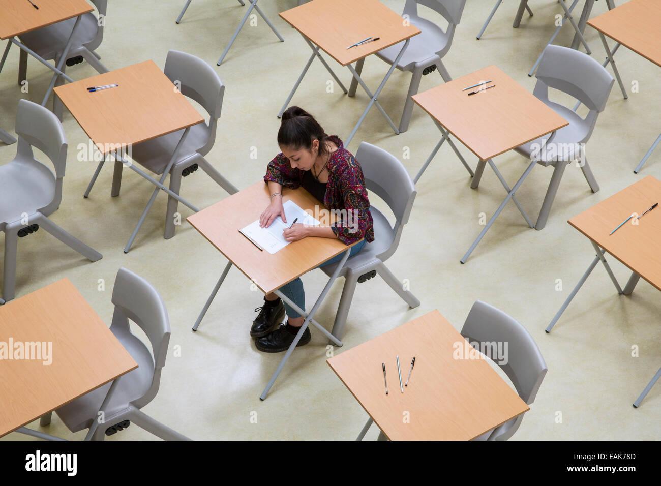 Erhöhten Blick auf einsamen Studentin schreiben ihre GCSE Prüfung im Klassenzimmer Stockbild