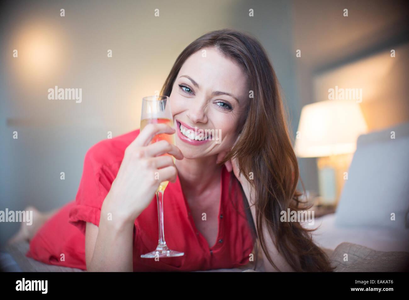 Porträt der lächelnde Frau auf Bett liegend mit Sektglas Stockfoto