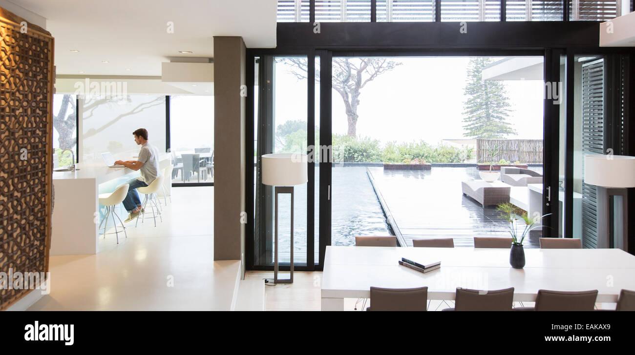 Junger Mann Mit Laptop In Moderne Küche, Ein Essbereich Mit Terrassentür  Und Pool Im Vordergrund