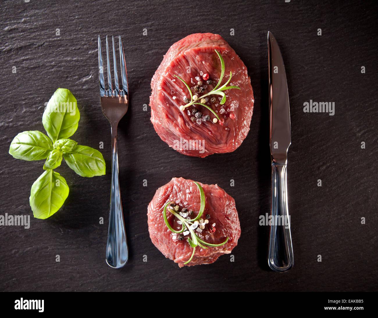 Stücke von roten rohes Fleisch Steaks mit Kräutern, serviert auf schwarzem Steinoberfläche. Erschossen Stockbild