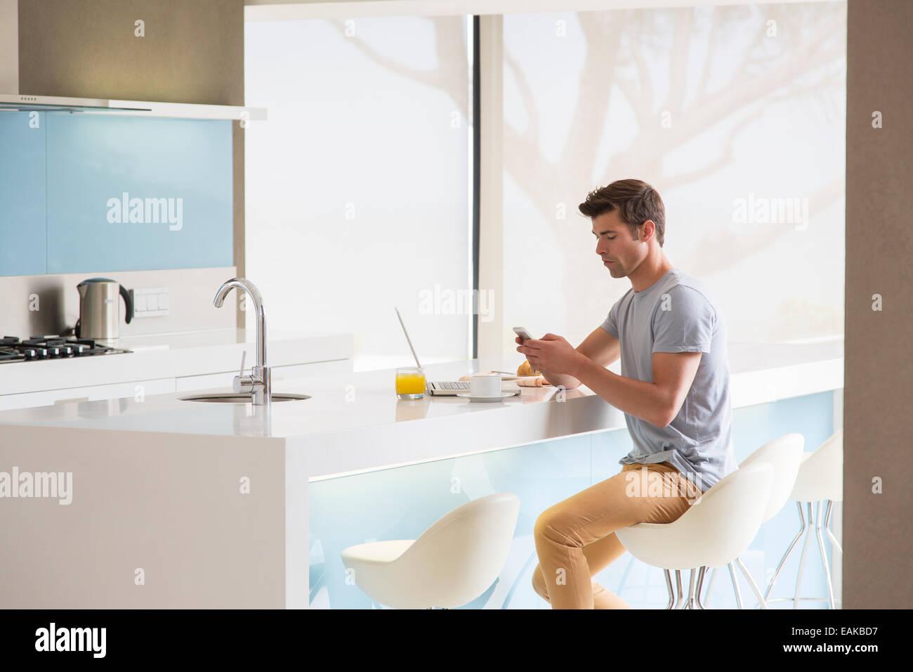Man sitzt auf Hocker an Kücheninsel und Telefon Stockfoto, Bild ...
