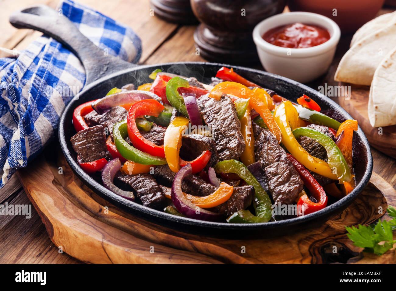 Beef Fajitas mit bunten Paprika in die Pfanne und Tortilla Brot und Soßen Stockbild