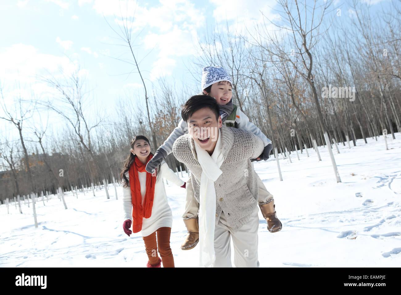 Eine Familie mit drei laufen im Schnee Stockbild
