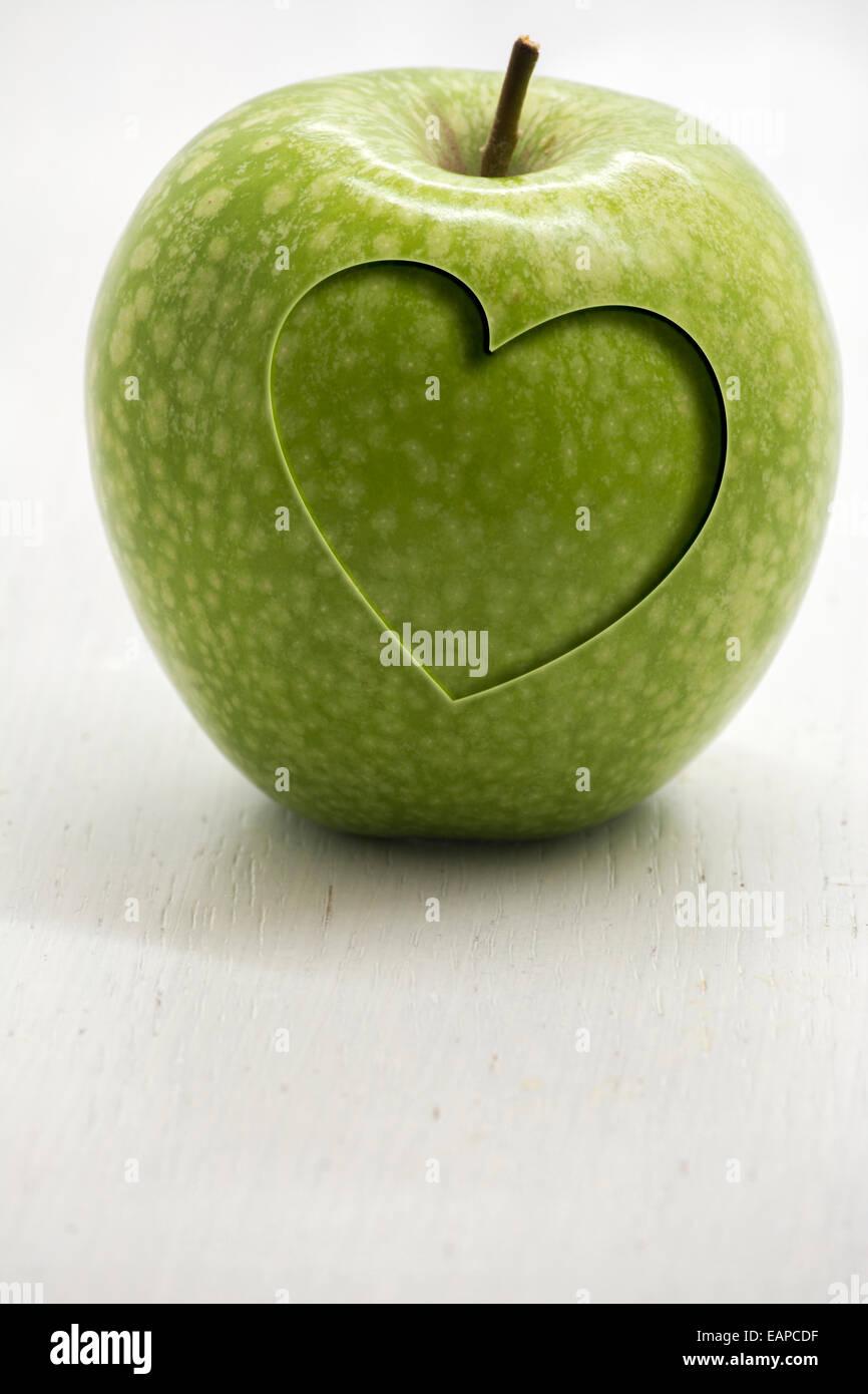 Grüner Apfel mit geschnitzten Herz, konzeptionelle Gesundheit und wellness Stockbild