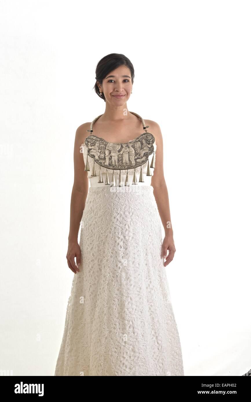 Hispanische Braut mit ihrem weißen Hochzeitskleid trägt eine ...
