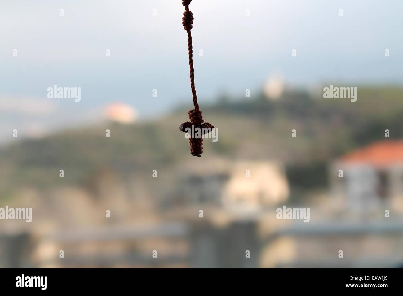 Eine hängende kleine verknotete Rosenkranz mit Kruzifix auf einen natürlichen Hintergrund. Stockbild